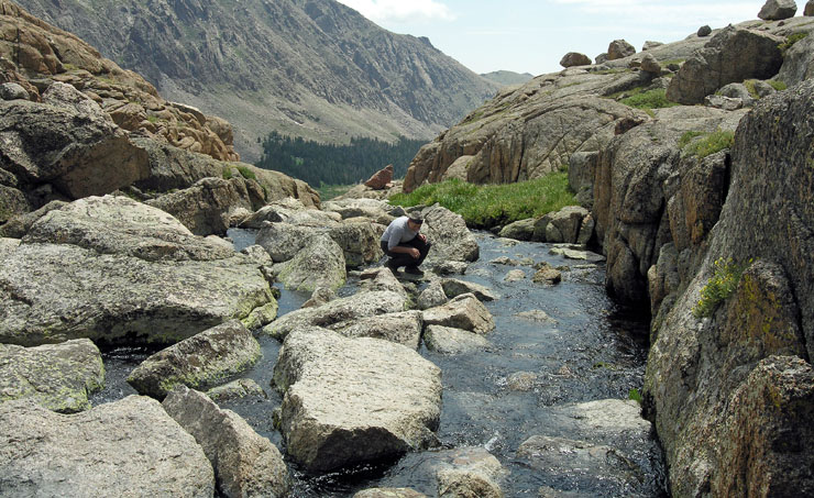 Suzy rock-hopping on creek watching Cutthroat trout at Crystal Lake