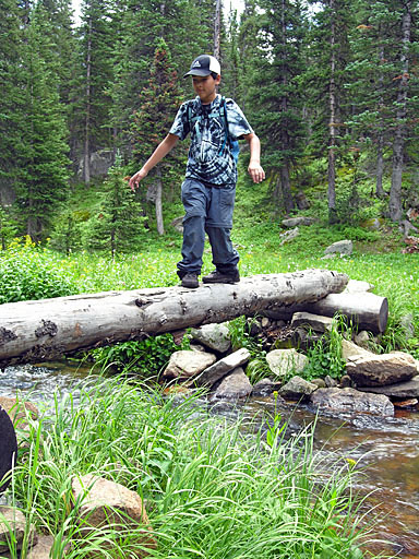 Christopher crossing creek below Mirror Lake on single-log bridge - Indian Peaks Wilderness Area, Colorado