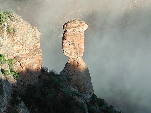 Balance Rock with fog rolling in under it, at the Colorado National Monument